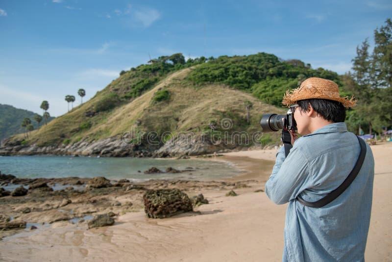 Jonge Aziatische mensenfotograaf die foto op het strand nemen royalty-vrije stock foto's