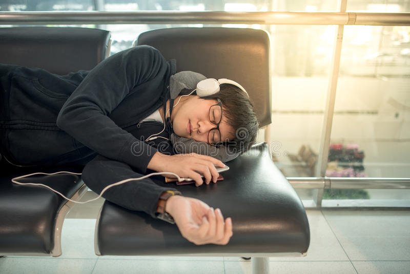 Jonge Aziatische mensenslaap op bank in luchthaventerminal royalty-vrije stock afbeelding