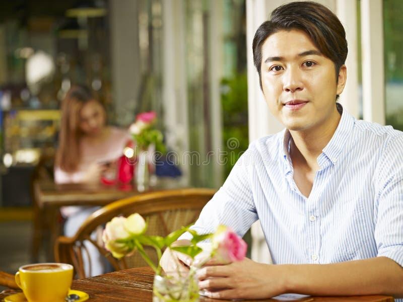 Jonge Aziatische mensenzitting in koffiewinkel stock foto