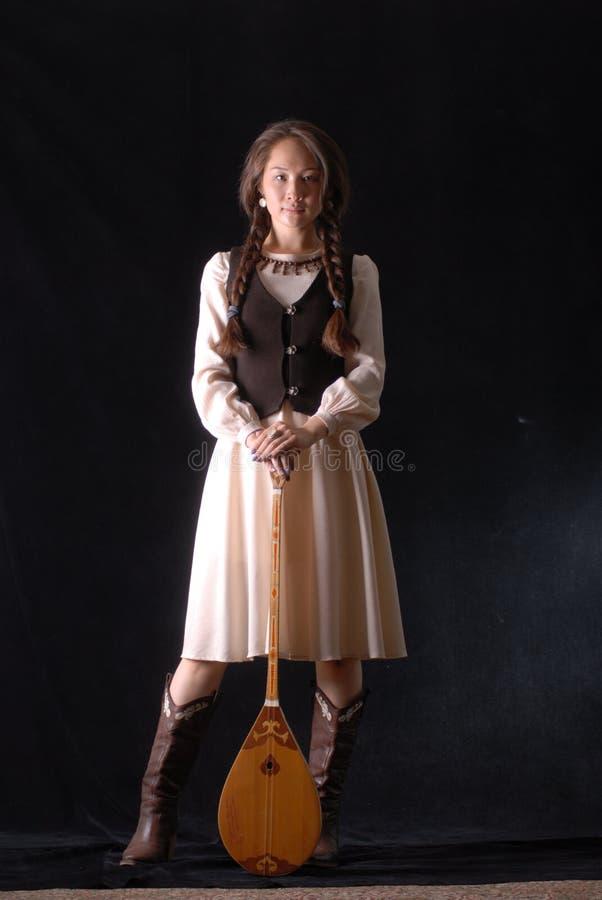 Jonge Aziatische modelin nationale kleding die zich in studio met komuz bevinden stock foto's