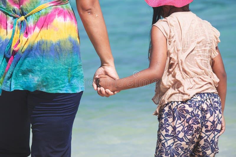 Jonge Aziatische moeder en leuk weinig hand van de dochterholding samen op het strand stock foto
