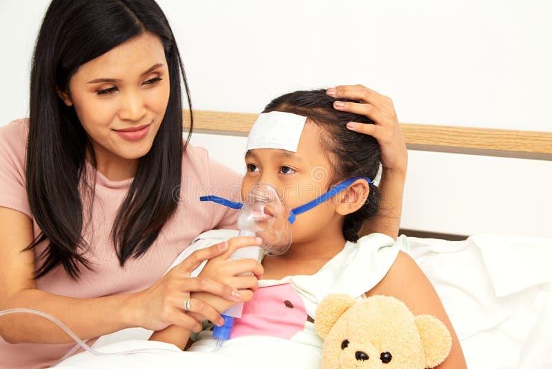 Jonge Aziatische moederzieke kinderverzorging stock foto