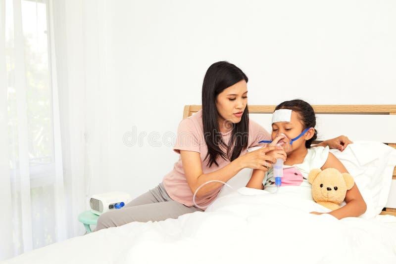 Jonge Aziatische moederzieke kinderverzorging stock fotografie