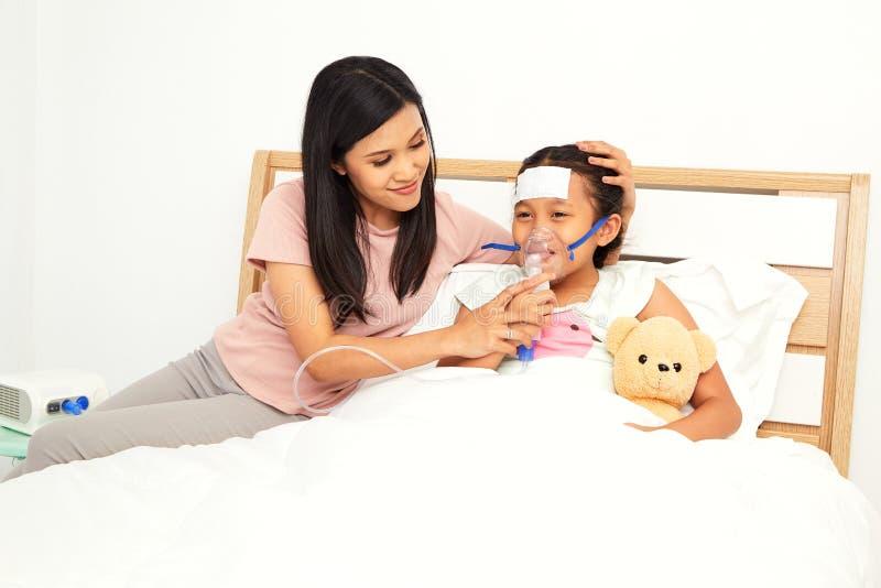 Jonge Aziatische moederzieke kinderverzorging stock afbeeldingen
