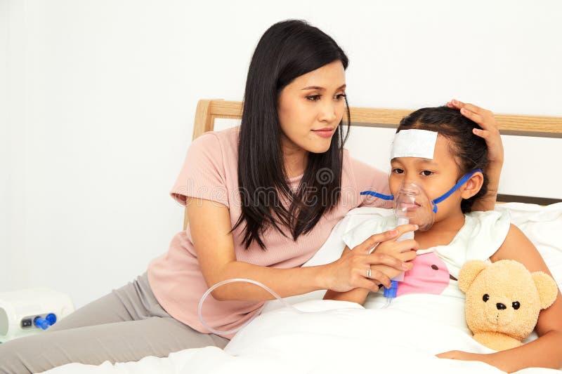 Jonge Aziatische moederzieke kinderverzorging royalty-vrije stock afbeeldingen