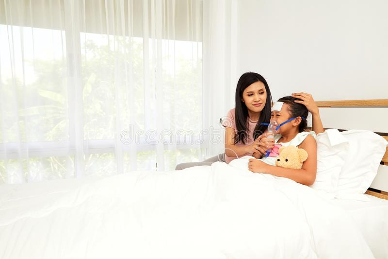 Jonge Aziatische moederzieke kinderverzorging royalty-vrije stock foto