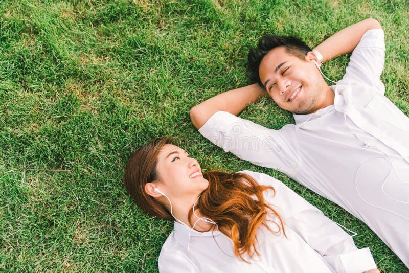 Jonge Aziatische mooie paar of studenten die samen op het gras liggen die, aan muziek, hoogste mening met exemplaarruimte luister stock afbeelding