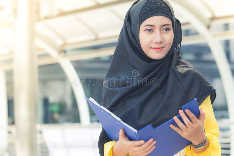 Jonge Aziatische moslim bedrijfsvrouw die en bedrijfsdossierdocument en zich bij hoofdstad glimlachen bevinden stock foto