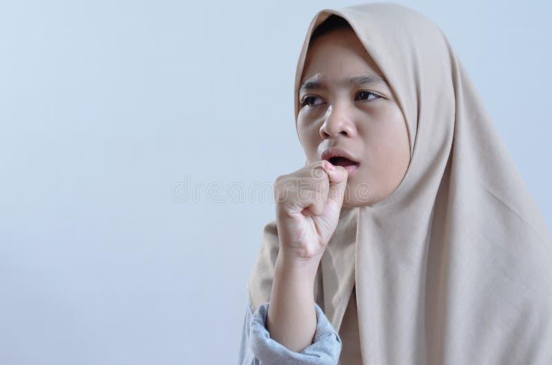 Jonge Aziatische moslimvrouwenzieken die met koude of keelpijn hoesten royalty-vrije stock foto