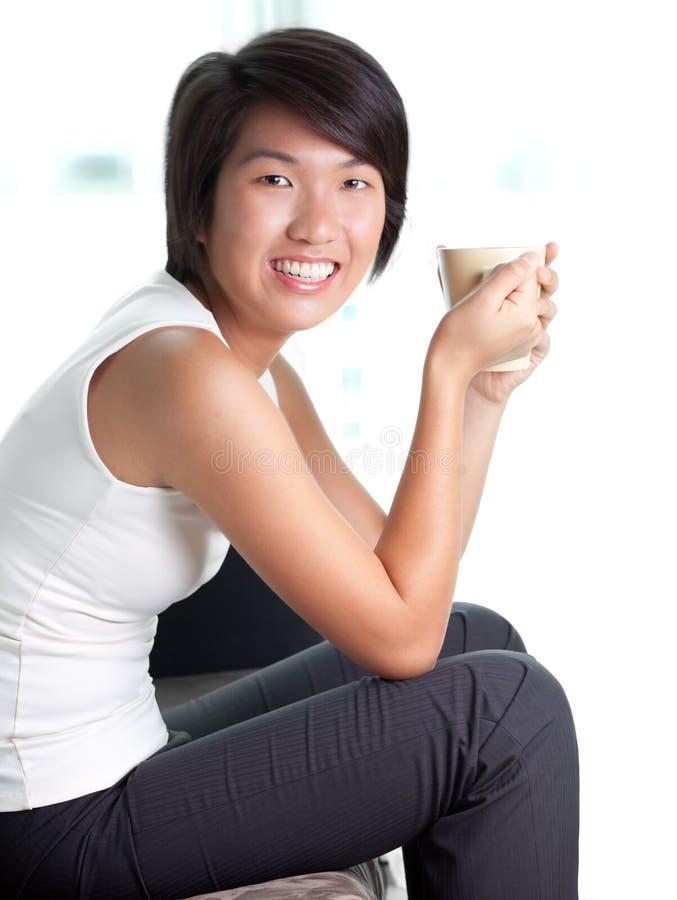 Jonge Aziatische onderneemster bij koffiepauze thuis stock foto