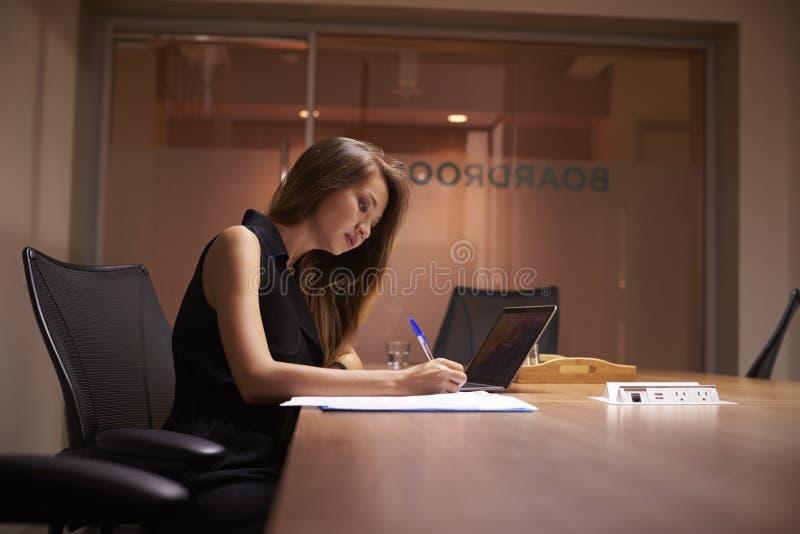 Jonge Aziatische onderneemster die alleen laat in een bureau werken stock fotografie