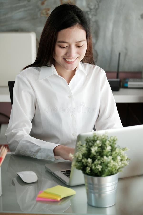 Jonge Aziatische onderneemster die met laptop computer op kantoor werken royalty-vrije stock fotografie