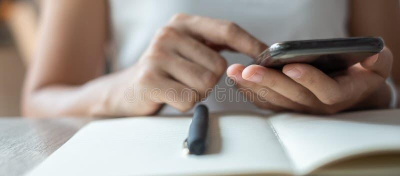 Jonge Aziatische Onderneemster die mobiele telefoon in bureau, vrouwenzitting en hand wat betreft het scherm op cellphone met beh royalty-vrije stock foto's
