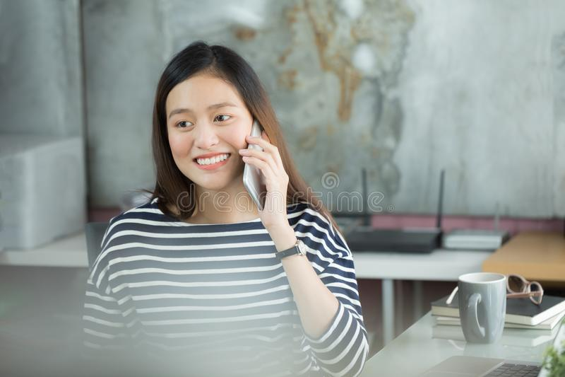 Jonge Aziatische onderneemster die smartphone gebruiken om met cust in wisselwerking te staan royalty-vrije stock fotografie