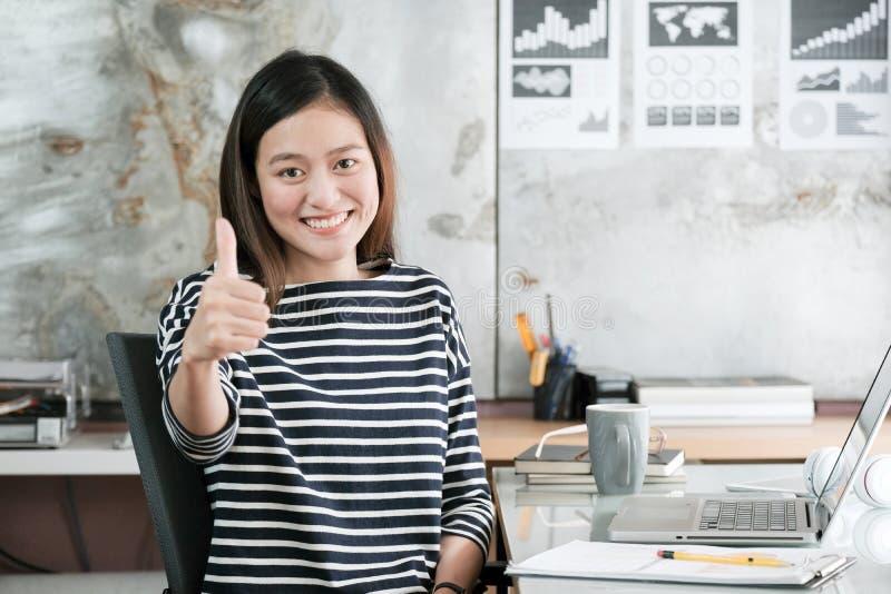 Jonge Aziatische onderneemsterdreun omhoog en glimlachend terwijl het zitten bij royalty-vrije stock fotografie