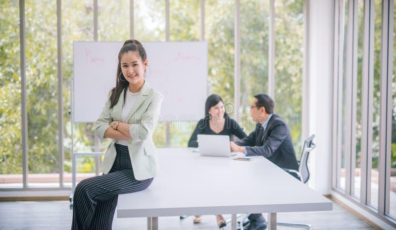 Jonge Aziatische onderneemsterzitting bij een bestuurskamer en het glimlachen bij de camera in een bestuurskamer met collega's op stock foto