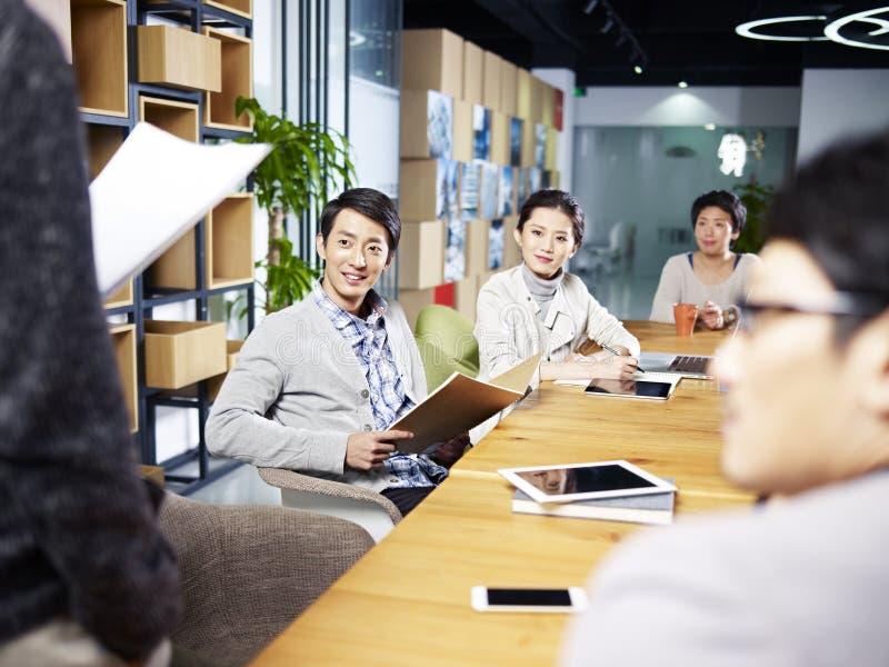 Jonge Aziatische ondernemers die in bureau samenkomen royalty-vrije stock afbeeldingen