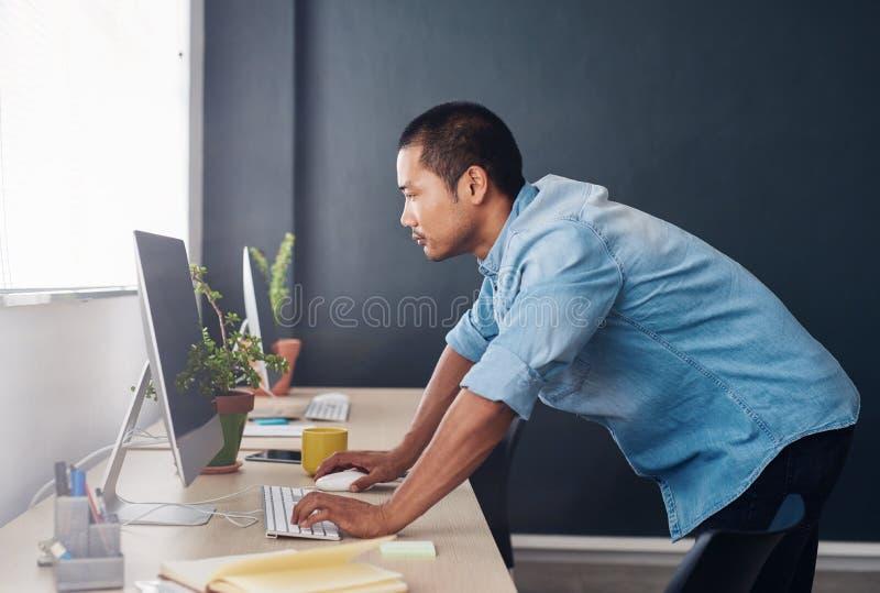 Jonge Aziatische ontwerper die zich bij zijn bureau bevinden die een computer met behulp van stock afbeelding