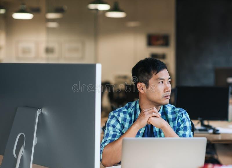 Jonge Aziatische ontwerperzitting bij zijn bureau die over het werk denken stock fotografie
