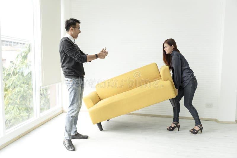 Jonge Aziatische paar bewegende bank in ruimte bij nieuw huis royalty-vrije stock afbeeldingen
