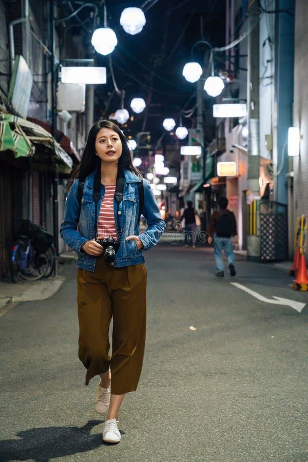 Jonge Aziatische reiziger die naar hotel bij nacht in Osaka Japan terugkeren vrouwelijke toerist met cameranacht uit op de donker royalty-vrije stock foto