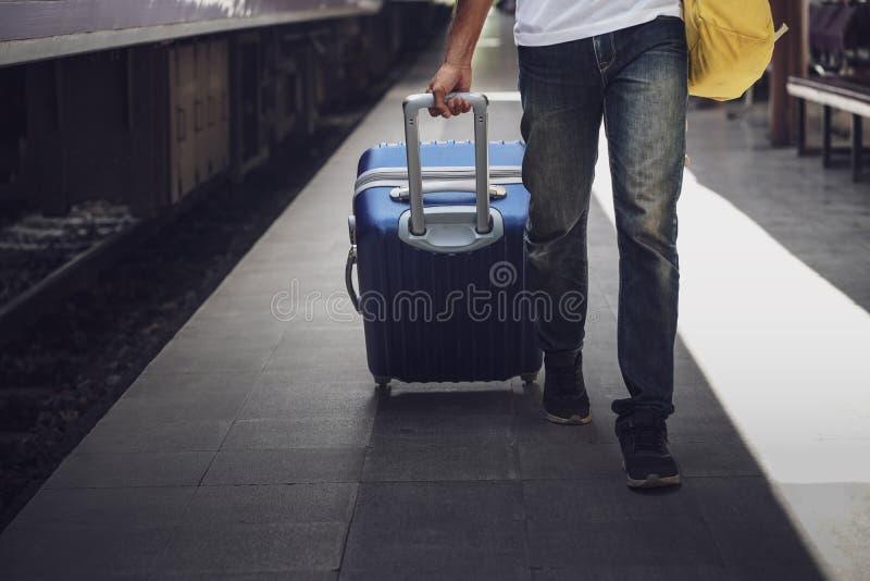 Jonge Aziatische reiziger met rugzak in de spoorweg, de toerist die van de Mensenreiziger met bagage bij station lopen Actief en  stock afbeelding