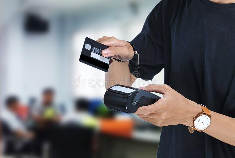 Jonge Aziatische student die een Elektronische Gegevensopslagedc machine houden en klaar om creditcard of debetkaart voor loon ov stock foto's