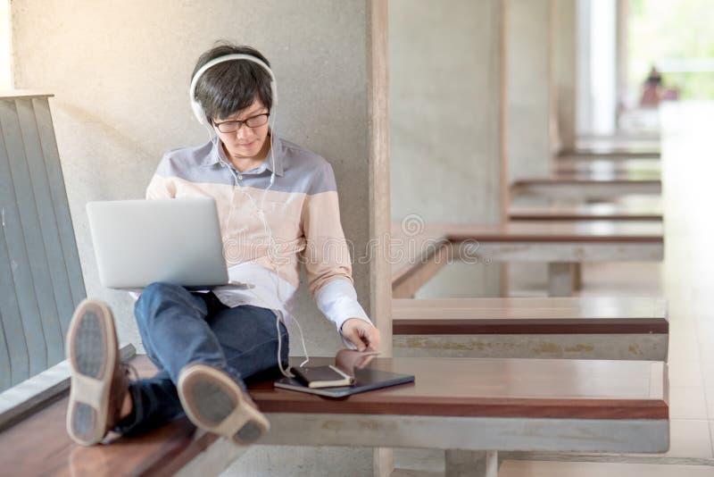 Jonge Aziatische studentenmens die laptop in universiteit met behulp van stock afbeelding