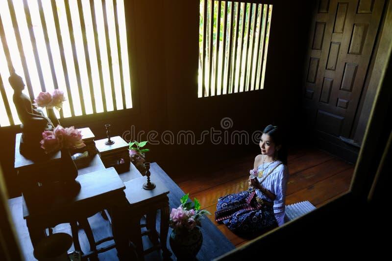 Jonge Aziatische Thaise vrouw die Boedha met lotusbloem in ruimte Boedha bidden stock foto's