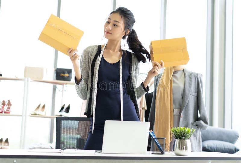 Jonge Aziatische toevallige bedrijfsvrouw die kleine het bedrijfs online werken met doos werken bij haar bureau, van het MKB en v royalty-vrije stock afbeelding