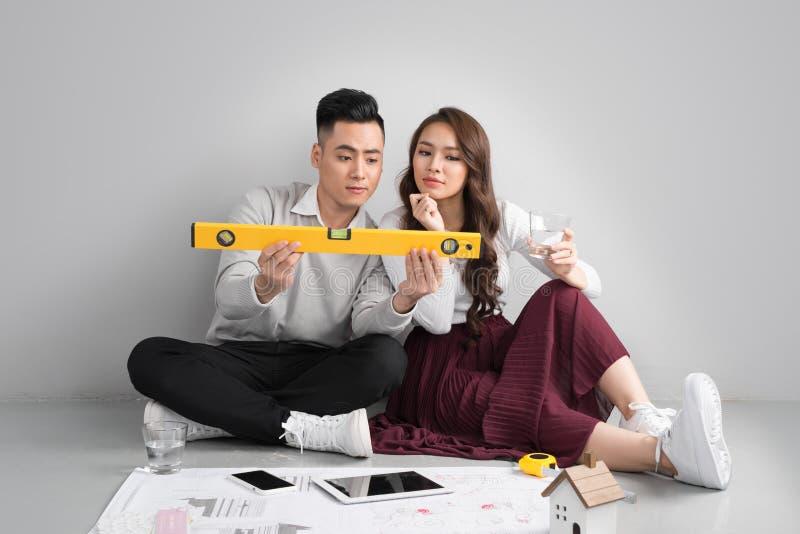 Jonge Aziatische volwassen paarzitting op Flor die nieuw huis plannen desig royalty-vrije stock foto's
