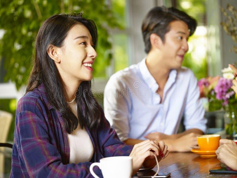 Jonge Aziatische volwassenen die aan vrienden in koffiewinkel spreken royalty-vrije stock afbeelding