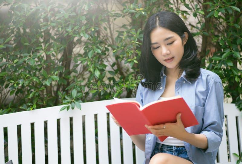 Jonge Aziatische vrouw die boek het ontspannen als voorzitter verder lezen bij tuin royalty-vrije stock afbeeldingen