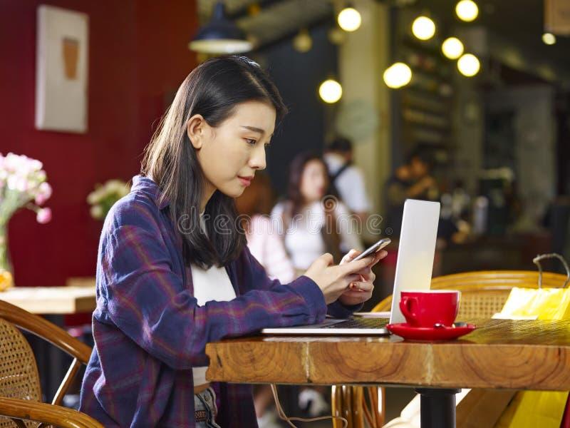 Jonge Aziatische vrouw die cellphone en laptop in koffiewinkel met behulp van stock foto's