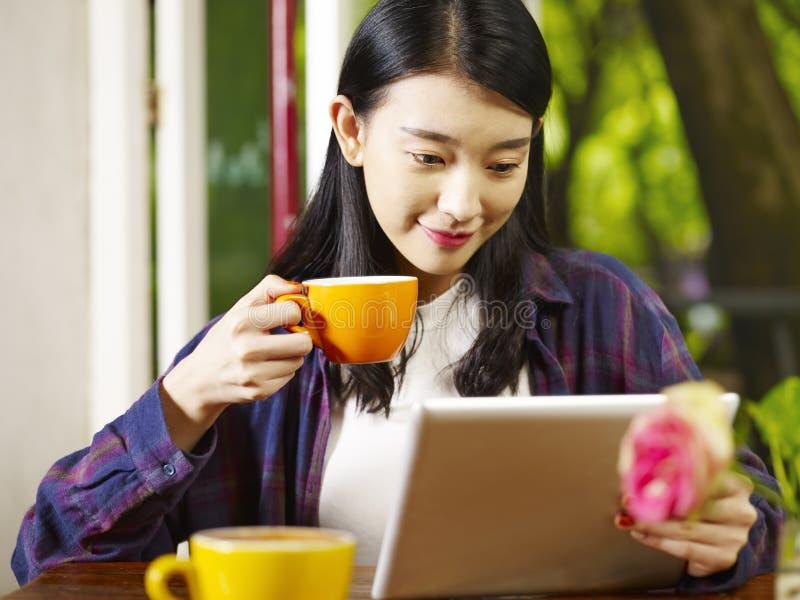 Jonge Aziatische vrouw die digitale tablet gebruiken terwijl het drinken van koffie stock foto