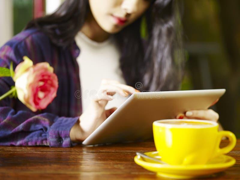 Jonge Aziatische vrouw die digitale tablet gebruiken terwijl het drinken van koffie royalty-vrije stock foto's