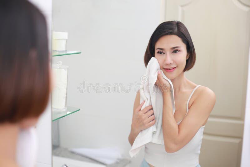 Jonge Aziatische vrouw die haar gezicht met handdoek in badkamers afveegt stock foto