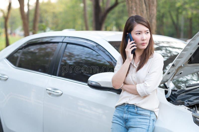 Jonge Aziatische vrouw die hulp voor haar opgesplitste auto roepen stock foto's