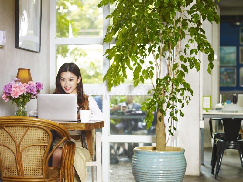 Jonge Aziatische vrouw die laptop computer met behulp van stock foto's