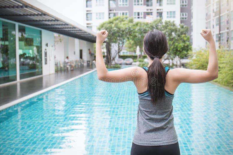 Jonge Aziatische vrouw die oefening doen door de pool in hotel of toevlucht stock foto's