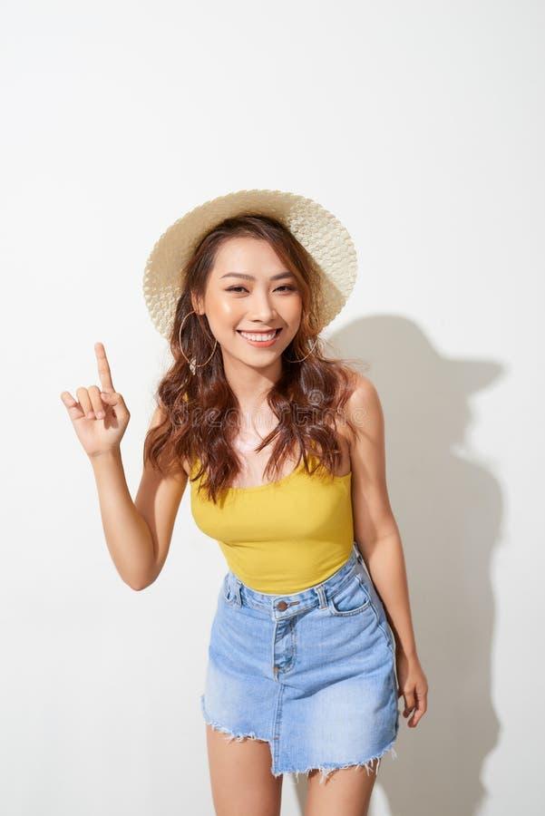 Jonge Aziatische vrouw die om hoed met uitdrukking van verrassing dragen die op witte achtergrond wordt ge?soleerd royalty-vrije stock fotografie