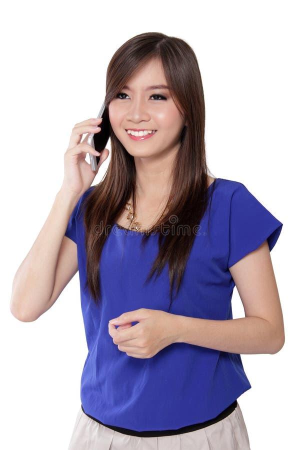 Jonge Aziatische vrouw die op die telefoon vooruit en glimlach kijken, op wit wordt geïsoleerd stock foto