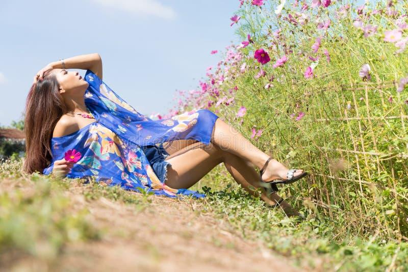 Jonge Aziatische vrouw die op het gebied van de Kosmosbloem liggen stock foto's