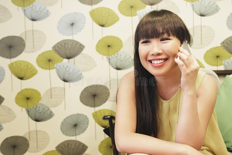 Jonge Aziatische vrouw die op smartphone spreken stock foto's