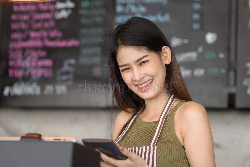 Jonge Aziatische vrouw die tablet gebruiken bij koffie royalty-vrije stock afbeelding