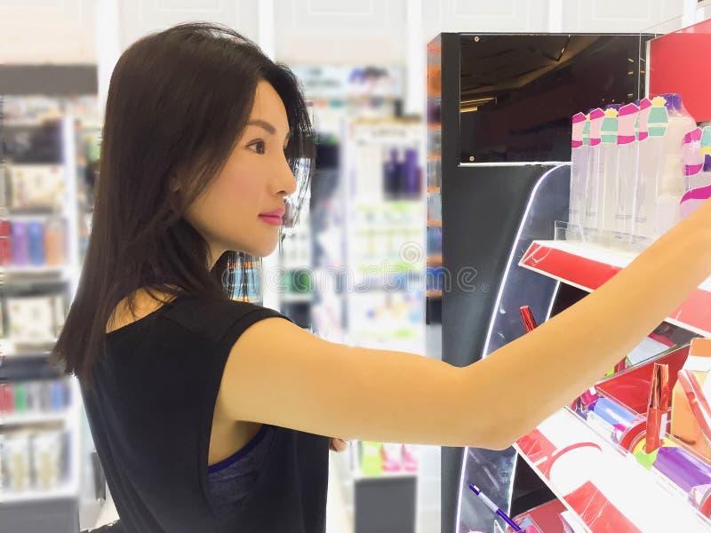 Jonge Aziatische vrouw die voor schoonheidsmiddel winkelen stock fotografie