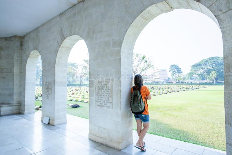 Jonge Aziatische vrouw die zich bij de overspannen ingang van Kanchanaburi-Oorlogsbegraafplaats Don Rak bevinden stock foto's