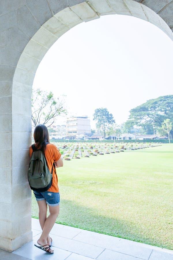 Jonge Aziatische vrouw die zich bij de overspannen ingang van Kanchanaburi-Oorlogsbegraafplaats Don Rak bevinden stock foto