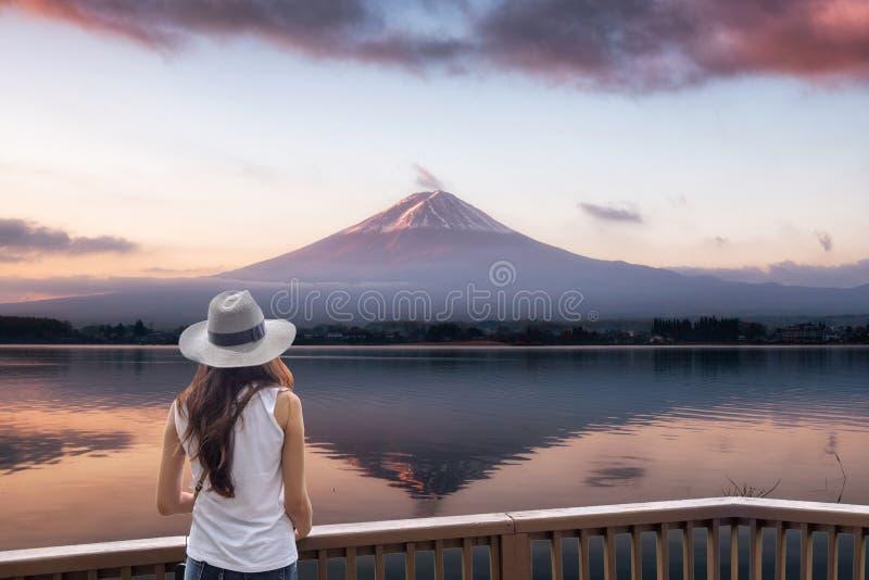 Jonge Aziatische vrouw die zich op houten balkon bevinden die fuji-San bergbezinning in meer dageraad bekijken royalty-vrije stock foto