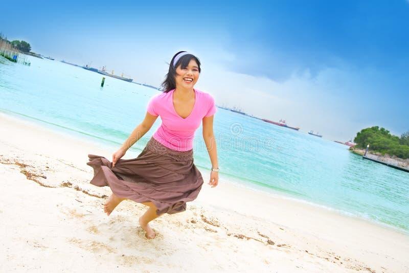 Jonge Aziatische vrouw door het strand stock afbeeldingen